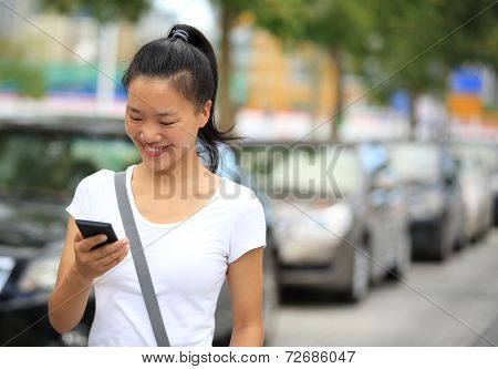 woman use her cellphone walking at parking lot