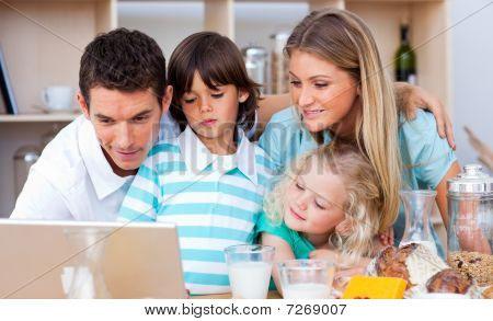Lovely Family Using Laptop During The Breakfast