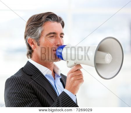 Confident Businessman Yelling Through A Megaphone
