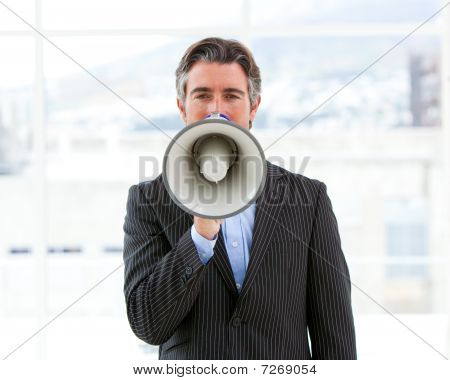 Mature Businessman Yelling Through A Megaphone