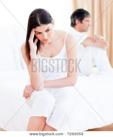 Upset Couple Having An Argument Sitting On Bed