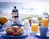 stock photo of orange-juice  - Lovely early morning breakfast table at the beach with focus on breakfast with sand and water blurred in the background - JPG