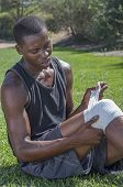 picture of knee-cap  - Lean muscular African American male athlete in shorts and tank top wraps injured knee with white sports bandage while sitting on grass - JPG