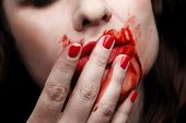 stock photo of finger-licking  - Female vampire licking blood off of her fingers - JPG
