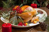stock photo of christmas dinner  - Roasted turkey garnished with sage rosemary and red berries in a tray prepared for Christmas dinner - JPG