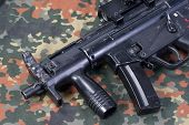 pic of mp5  - modern 9 mm submachine gun on camouflaged background - JPG