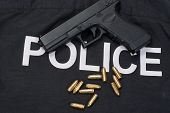 image of ammo  - 9mm handgun with ammo on police uniform - JPG