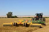 image of cultivator-harrow  - A tractor pulls a disc harrow system implement to smooth over a dirt field in preperation for planting in central California - JPG