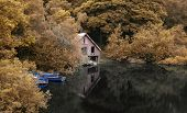 pic of derelict  - Derelict old boathouse and rowing boats hidden in forest lake in Autumn - JPG