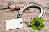 pic of horseshoe  - Horseshoe shamrock and champagne cork with empty tag on old wooden - JPG
