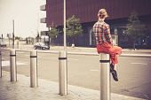 stock photo of bollard  - A young woman is sitting on a bollard by the roadside in the city - JPG