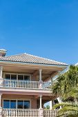 stock photo of balustrade  - Verandas on a pink stucco beach home with white balustrade under blue sky - JPG