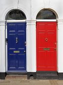 stock photo of cornerstone  - Red and blue front doors with victorian design archhitraves - JPG