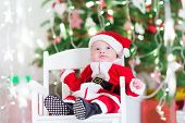 picture of santa baby  - Little Newborn Baby Boy In Santa Outfit Sitting Under A Christmas Tree - JPG