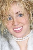 image of chokers  - A beautiful smiling young woman with blond hair and blue eyes wearing a pearl choker and fake fur coat - JPG