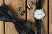 picture of tuxedo  - Directly above view of a old wooden table bowtie cufflinks and wristwatch on it - JPG