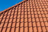 stock photo of red roof tile  - Red roof tiles of a new house on blue sky - JPG