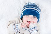 foto of blanket snow  - Funny Laughing Baby In A Blue Knitted Hat And A Warm Sweater - JPG