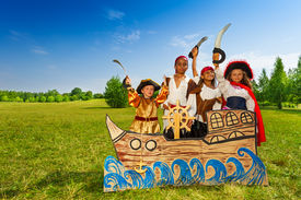 stock photo of pirate sword  - Happy diversity group of children in pirate costumes with swords standing behind ship made of cardboard - JPG