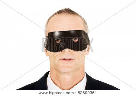 Serious mature businessman wearing eye mask