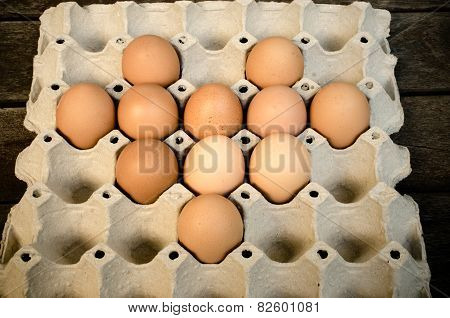Eggs laid out on a tray on wooden background