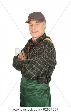 Experienced smiling gardener standing with folded arms