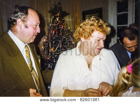 Vintage photo of elderly woman blessing her family and sharing Christmas wafer during Christmas Eve Vigil, eighties