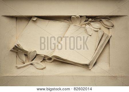 Medieval book. Stucco decoration on the Art Nouveau building in Prague, Czech Republic.