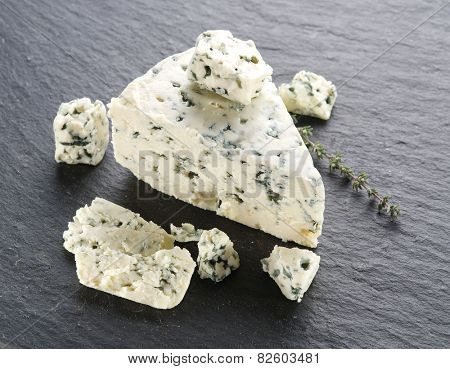 Slices of Danish Blue cheese on the gray stone surface.