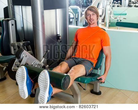 Leg extension exercise man at gym indoor workout