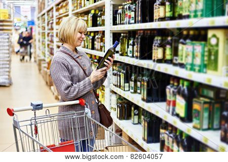 Woman Reading Label On Bottle Of Olive Oil In Store