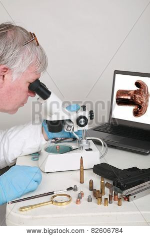 forensic analysis - a forensics lab technician examines a bullet and hand gun for finger prints, blood splatter, and any other residue or evidence to be used in a court case