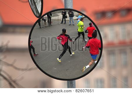 PRAGUE, CZECH REPUBLIC - APRIL 6, 2013: Convex mirror with the reflection of athletes running the Prague international marathon in Prague, Czech Republic.