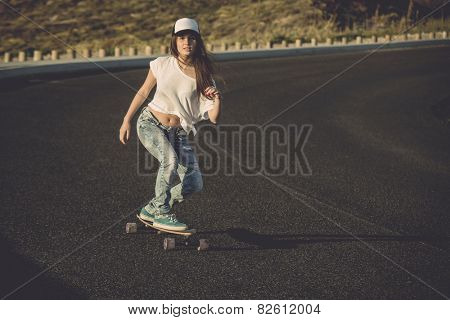 Young woman making downhill with a skateboard