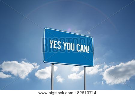The word yes you can! and blue billboard sign against cloudy sky with sunshine