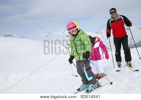 Family skiing down ski slope in winter
