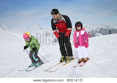 Ski teacher helping young kids to go down ski slope