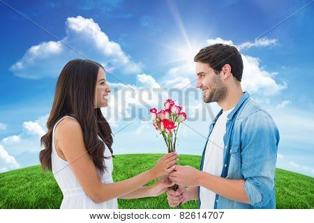Happy hipster giving his girlfriend roses against green hill under blue sky