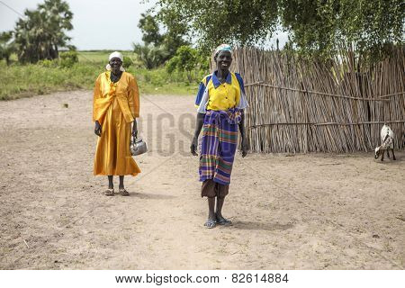 PANWELL, SOUTH SUDAN-NOVEMBER 2, 2013: Unidentified women in colorful dress go about their business in a small village in South Sudan