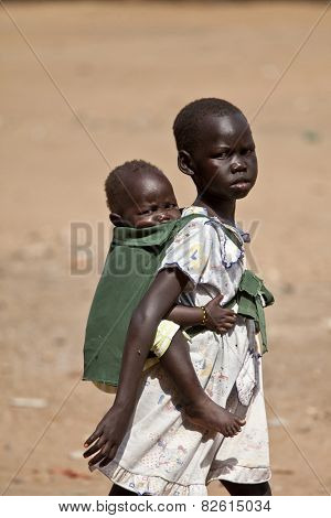 TORIT, SOUTH SUDAN-FEBRUARY 20, 2013: Unidentified little girl carries her sister on her back in South Sudan