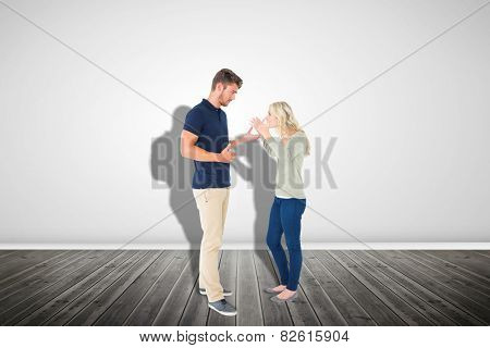 Young couple having an argument against grey room