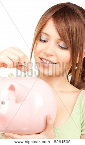 Lovely Teenage Girl With Piggy Bank And Coin