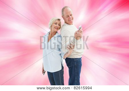 Happy mature couple looking at smartphone together against digitally generated girly heart design