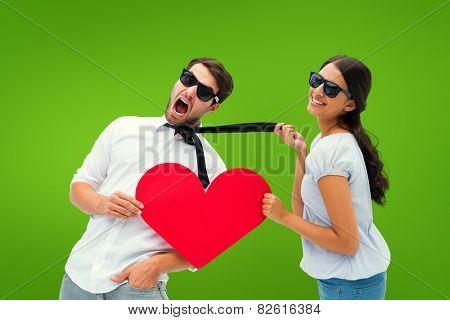 Brunette pulling her boyfriend by the tie holding heart against green vignette