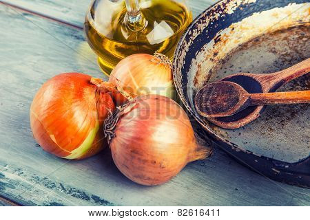 Old kitchen pan wooden spoon three onions on wooden table. Some of the equipme