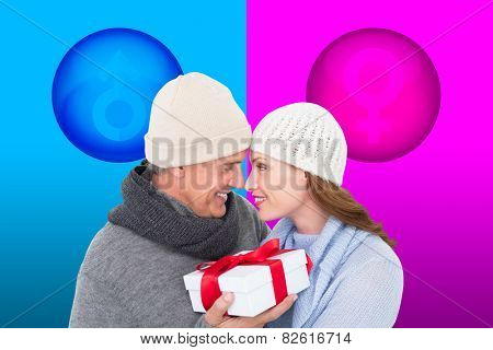 Casual couple in warm clothing holding gift against female gender symbol
