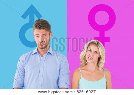 Young couple making silly faces against pink and blue