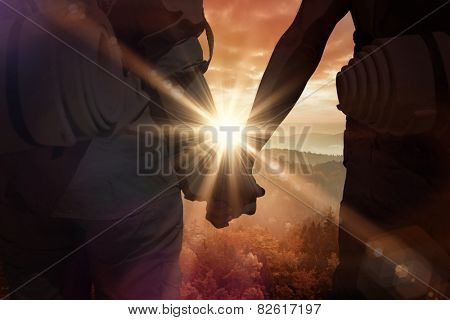 Hitch hiking couple standing holding hands on the road against sunrise over mountains