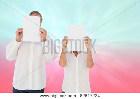 Couple holding paper over their faces against blue and pink light spot design