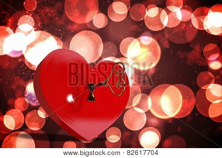 Love heart lock against twinkling red and orange lights